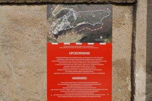 Upozornenie na zákaz voľného pohybu v podhradí na múre podhradského cintorína osadilo mesto.