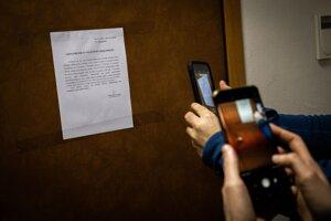 Novinári si fotia oznámenie o vylúčení verejnosti na dverách pojednávacej miestnosti v Justičnej akadémii v Pezinku.