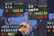 Muž kráča okolo elektronickej tabule s vývojom ukazovateľov japonských akcií v Tokiu.