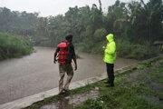 Záchranári stoja pri rozvodnenej rieke v blízkosti indonézskeho mesta Yogyakarta.