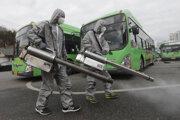 Pracovníci v ochranných odevoch dezinfikujú proti koronavírusu autobusové parkovisko - ilustračná fotografia.