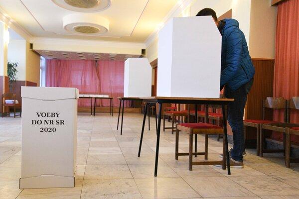 Volič vo volebnej miestnosti v Starej Turej hlasuje za plentou v rámci volieb do Národnej rady SR 2020.