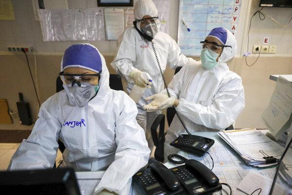 Na snímke zdravotník dezinfikuje proti koronavírusu ruky kolegom v nemocnici v ránskom Teheráne.