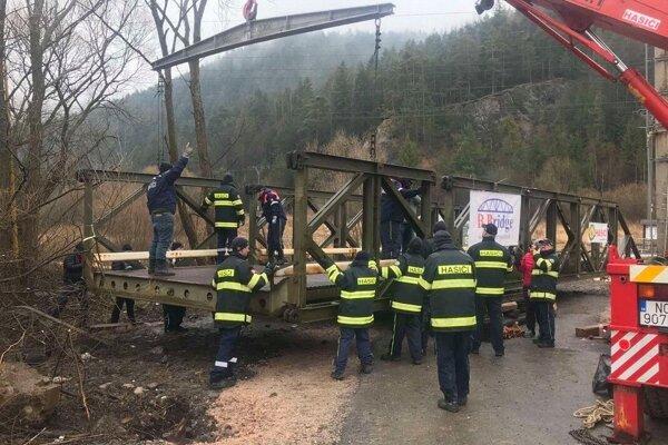 Pri stavaní dočasného mosta asistuje aj polícia, ktorá zabezpečuje bezpečnosť a plynulosť na ceste.