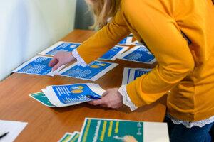 Zamestnankyne zariadení žilinskej župy si preberajú informačné letáky počas praktickej ukážky hygieny rúk v rámci školenia pre zníženie rizika šírenia nebezpečných nákaz.
