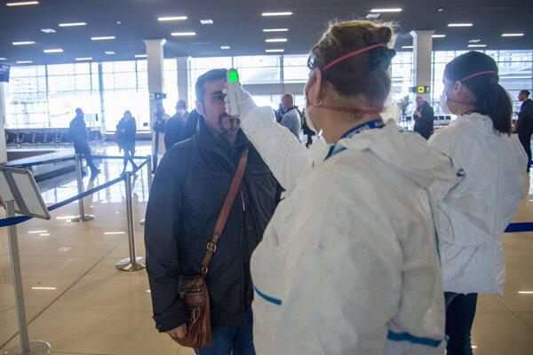 Zdravotný personál kontroluje telesnú teplotu cestujúceho, ktorý priletel na bratislavské Letisko M. R. Štefánika.