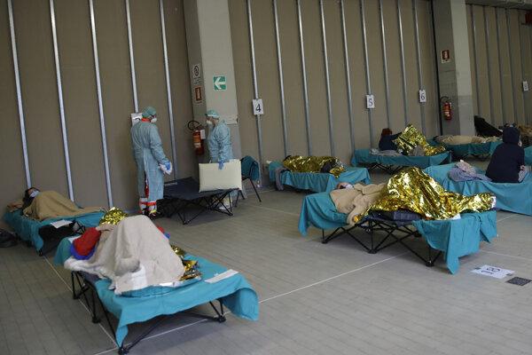 Pacienti ležia na posteliach v jednom zo stanov pred nemocnicou v talianskom meste Brescia.