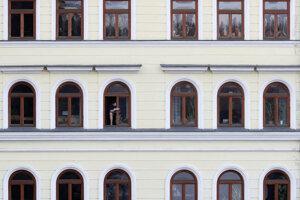 Muž sa pozerá z okna neďaleko Karlovho mosta v pondelok 16. marca 2020 v Prahe.