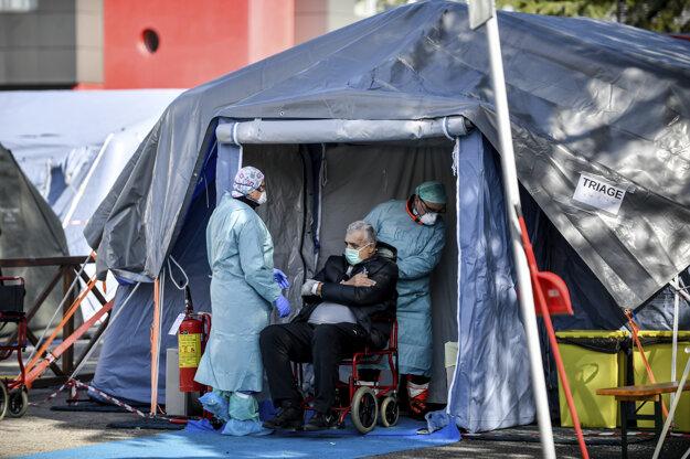 10. marec 2020: Zdravotníci pomáhajú staršiemu pacientovi do jedného zo stanov pred nemocnicou v talianskom meste Brescia.