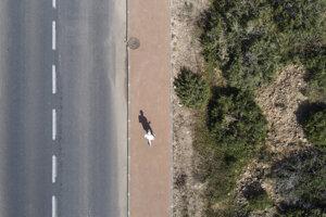 Muž kráča po prázdnej ulici v izraelskom meste Hadera.