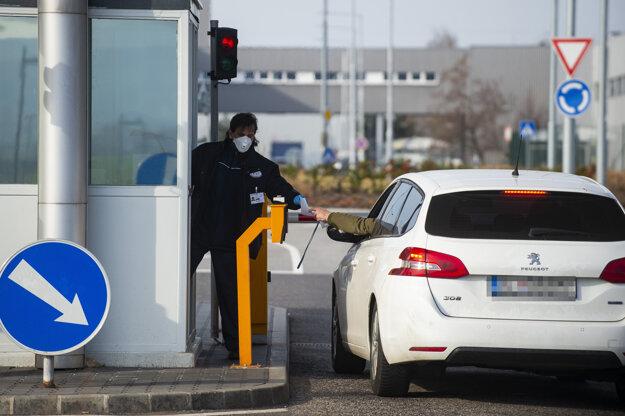 Zamestnanci automobilky Volkswagen Slovakia prechádzajú kontrolou pri vstupe do areálu.