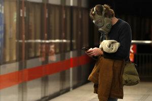 Muž so starou vojenskou plynovou maskou na tvári z dôvodu šíriaceho sa koronavírusu čaká na metro v Prahe.
