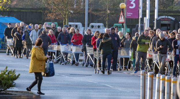 Zákazníci stoja v rade pred otvorením supermarketu v Liverpoole 20. marca 2020.
