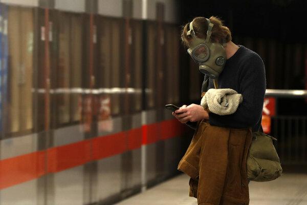 Muž so starou vojenskou plynovou maskou na tvári z dôvodu šíriaceho sa koronavírusu čaká na metro v Prahe 17. marca 2020.