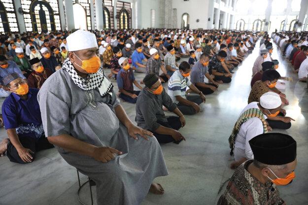 Moslimskí muži s rúškami na tvárach a v metrových odstupoch kvôli prevencii pred nákazou koronavírusom sa zúčastňujú na piatkovej modlitbe v mešite Al Akbar v indonézskom meste Surabaja.