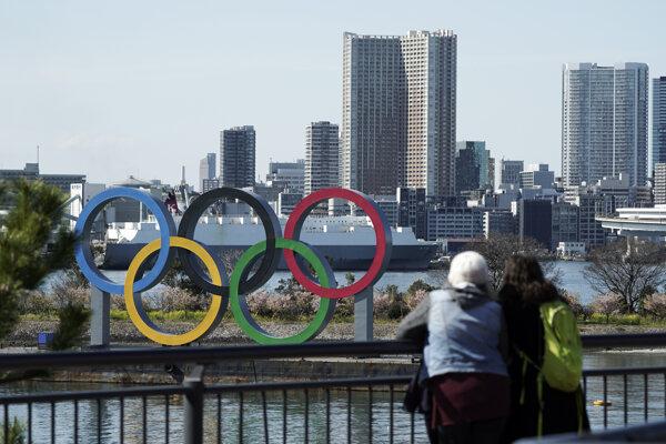Turisti hľadia na panorámu Tokia s olympijskými kruhmi.