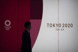 Muž kráča okolo reklamného transparentu tohtoročných letných olympijských hier v Tokiu v pondelok 23. marca 2020.
