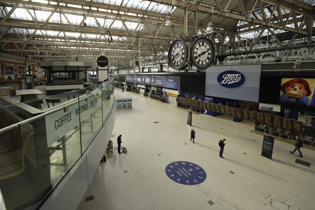 Len niekoľko cestujúcich kráča po prázdnej stanici metra Waterloo v Londýne.