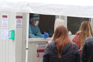 Pacienti čakajú v rade pri kontajneri na testovanie výskytu ochorenia COVID-19 pred Univerzitnou nemocnicou Bratislava.