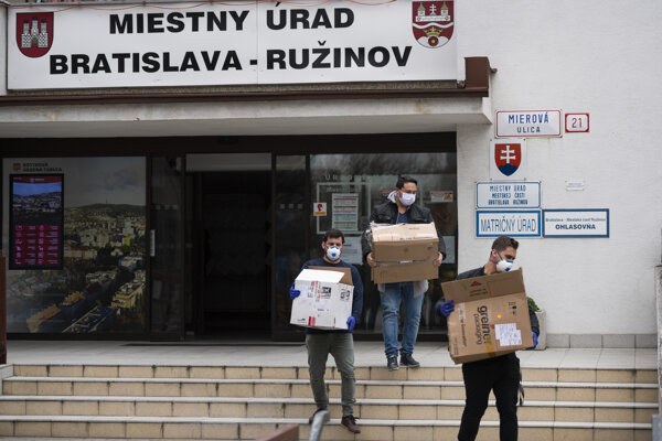 Starosta mestskej časti Bratislava-Ružinov Martin Chren si prevzal 3000 kusov jednorázových ochranných rúšok, ktoré následne budú distribuovať pomocou taxislužby najviac ohrozeným spoluobčanom. Na snímke muži nesú krabice s jednorázovými ochrannými rúškami v Bratislave 26. marca 2020.