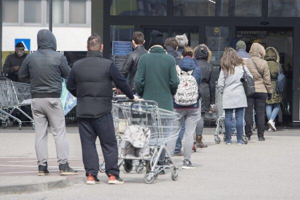 Čakajúci ľudia stoja v rade pred obchodom v Bratislave.