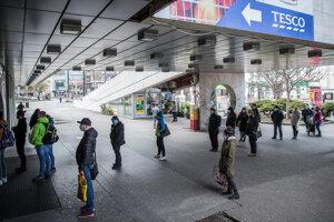 Ľudia pred obchodmi dodržiavajú odstup.