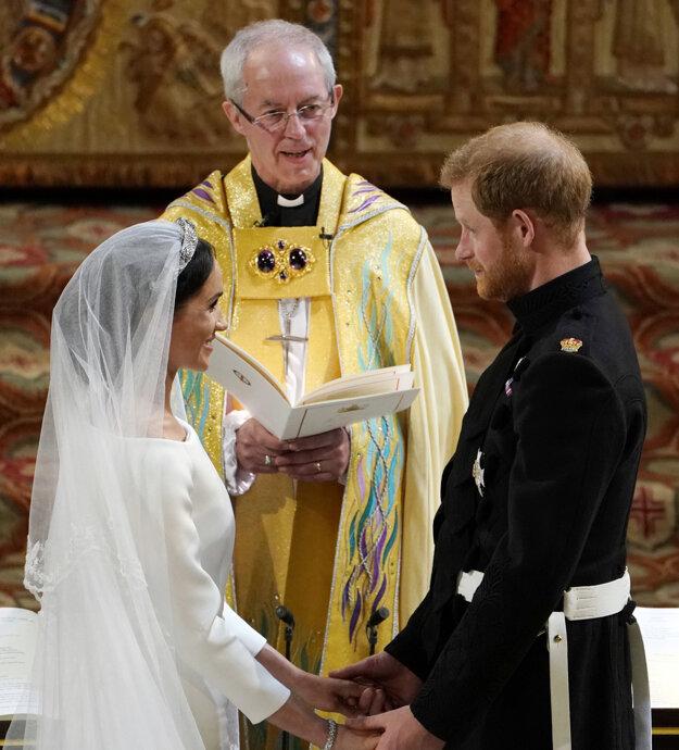 Ženích britský princ Harry, vľavo nevesta Meghan Markleová, uprostred arcibiskup z Canterbury Justin Welby počas manželského sľubu v rámci sobášneho ceremoniálu v Kaplnke sv. Juraja na kráľovskom zámku vo Windsore.
