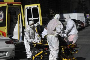 Zdravotný personál v špeciálnych ochranných odevoch vynáša zo sanitky pacienta s koronavírusom pred nemocnicou v Budapešti.