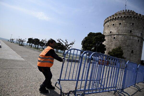 Mestský pracovník inštaluje oplotenie počas zákazu vychádzania pred Bielou vežou v Thessaloniki.