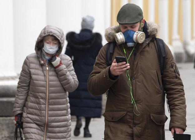 Koronavírus: Ľudia s ochranným rúškom a maskou na tvári kráčajú na ulici v Petrohrade.