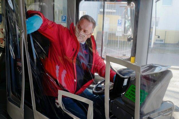 Vodič autobusu MHD v Poprade zaťahuje zips na plastovom ochrannom štíte proti šíreniu nového koronavírusu.