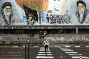 Muž prechádza cez prázdnu ulicu v iránskom Teheráne.
