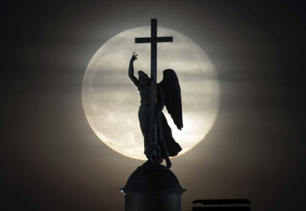 Silueta sochy anjela na hrote Alexandovhoho stĺpa s Mesiacom v splne na námesti v Petrohrade v Rusku.
