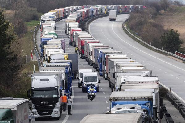 Nemeckí policajti jazdia na motorke medzi kamiónmi počas kolóny na diaľnici A4 neďaleko nemeckého Görlitzu.