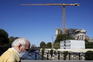Muž s ochranným rúškom na tvári kráča okolo parížskej katedrály Notre-Dame.
