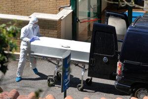 Pracovník v ochrannom odeve odváža rakvu z rezidencie a hospicu San Raffaele v meste Rocca di Papa 15. apríla 2020.