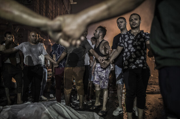 Oliver Weiken (DPA) získal tretiu cenu v kategórii Spot News Stories. Muži stoja okolo tela obete bombového útoku v Egypte v Káhire