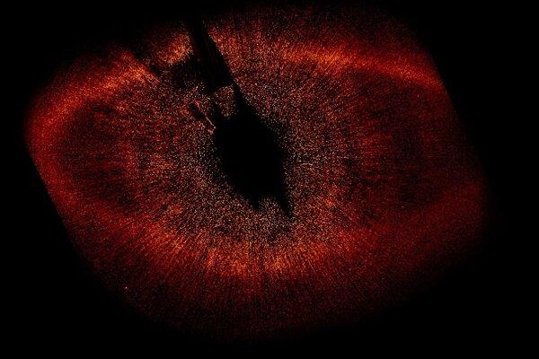 Prachový prstenec, zobrazený  červenou farbou, obklopuje hviezdu Fomalhaut,  ktorá sa nachádza  uprostred snímky, nie je viditeľná voľným okom a je vzdialená 25 svetelných rokov od Zeme.