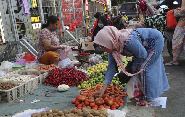 Žena s ochranným rúškom na zabránenie šíreniu nového koronavírusu nakupuje zeleninu na pouličnom trhu v Jakarte 24. apríla 2020
