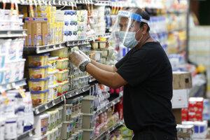 Predavač s ochranným štítom dopĺňa zásoby v potravinách v Dallase.