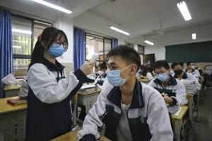 Študentka v rúšku meria teplotu svojim spolužiakom na škole v čínskom Wu-chane.