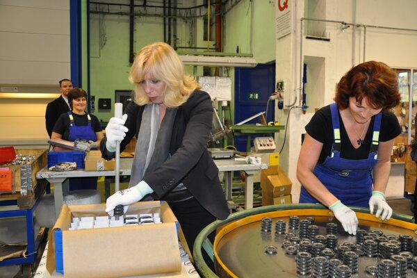 Bývalá premiérka Iveta Radičová (vľavo) si počas návštevy podniku Miba Sinter SLovakia v Dolnom Kubíne vyskúšala prácu pri jednom zo strojov.