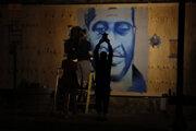 Umelec maľuje na stenu portrét Georgea Floyda.
