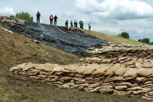 Podmočené hrádze spevňovalo vojsko i dobrovoľníci. Vrecovanie pri rieke Latorica.
