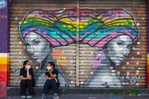 Ženy sa rozprávajú pred zatvorenou predajňou s oblečením počas koronavírusovej pandémie v brazílskom veľkomeste Sao Paulo 1. júna 2020.