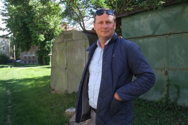 Peter Kellner pred plechovými garážami, na ktorých je azbest. Zaberajú trávnik, nikto ich nevyužíva.