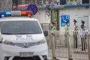Polícia pred tržnicou v Pekingu.