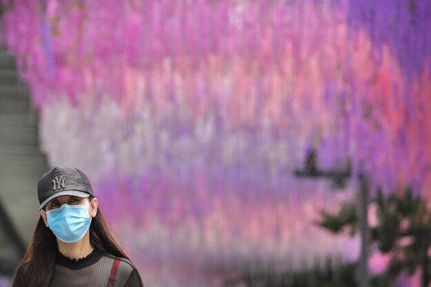 Žena s ochranným rúškom v centre Pekingu.