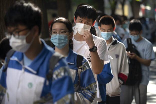Mladí Číňania v rúškach čakajú v rade počas prvého dňa vstupných testov na univerzity.