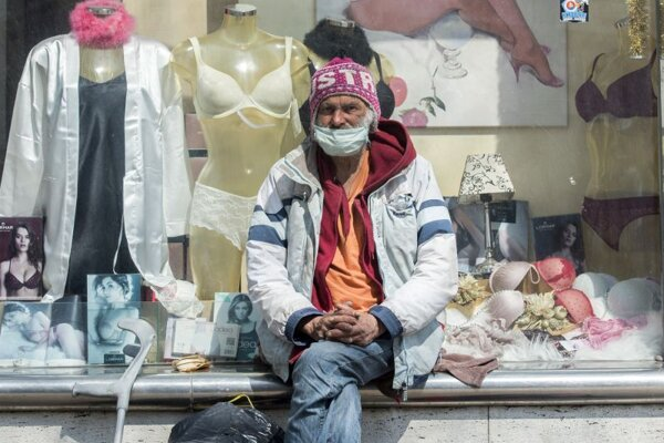 Bezdomovec s ochranným rúškom na tvári sedí na Námestí SNP v Bratislave.